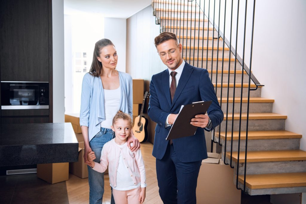 attractive woman standing with daughter and looking at broker